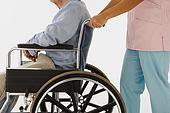 42-16902295 - Nurse pushing man in wheelchair